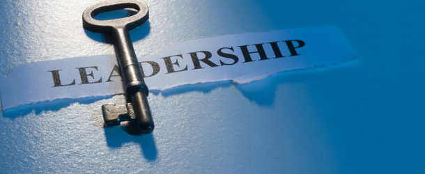 "A key laying on a piece of paper with the word ""leadership"" on it."