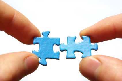 Hands holding two  puzlle on white